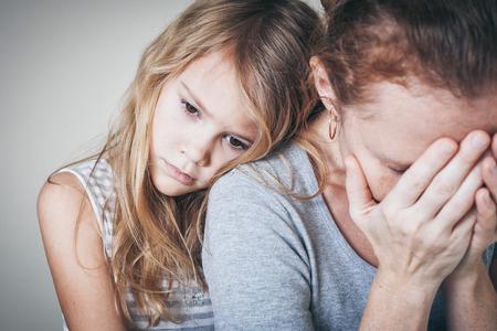 ansiedad: hija triste que abraza a su madre en el hogar. Concepto de familia pareja está en el dolor. Foto de archivo