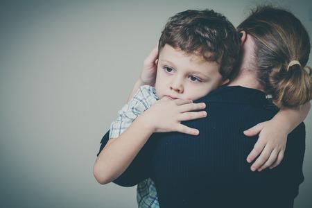nešťastný: smutný syn objímá svou matku doma. Koncepce pár rodina je ve smutku.