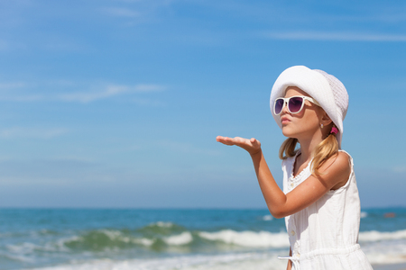 lifestyle caucasian: Little girl  standing on the beach at the day time Stock Photo
