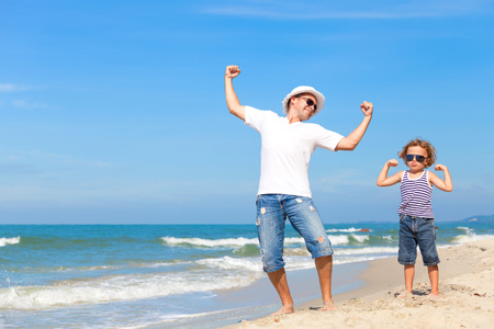 couple relaxing: Father and son playing on the beach at the day time. Concept of friendly family.
