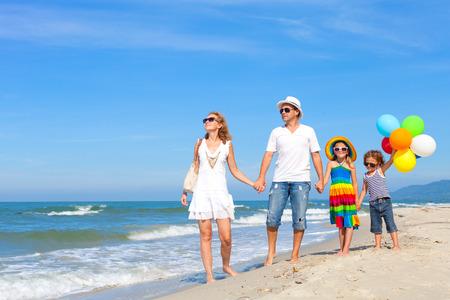 familia viaje: Familia feliz jugando con globos en la playa en el día. Concepto de la familia.