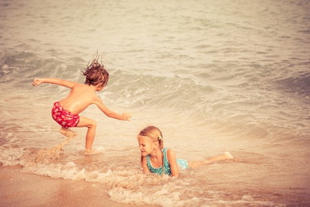 brothers: Sister and brother playing on the beach at the day time. Concept Brother And Sister Together Forever
