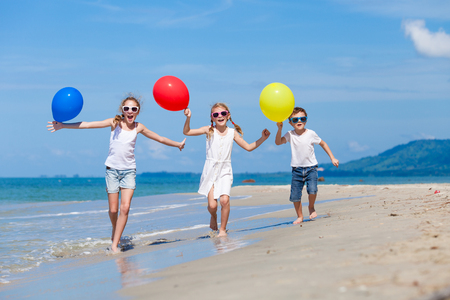 viaje familia: Tres niños felices con globos runing en la playa en el tiempo del día. Concepto de familia feliz de amigos.