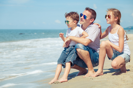 niños sentados: Padre y niños que se sientan en la playa en el tiempo del día. Concepto de familia feliz de amigos. Foto de archivo