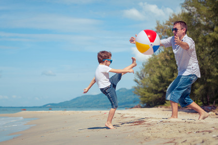 Father and son with ball playing soccer on the beach at the day time. Concept of friendly family. Archivio Fotografico