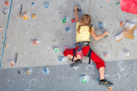 niño escalando: niña que sube una pared de roca cubierta Foto de archivo
