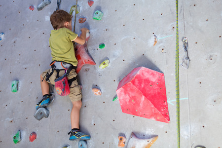 rock wall: little boy climbing a rock wall indoor