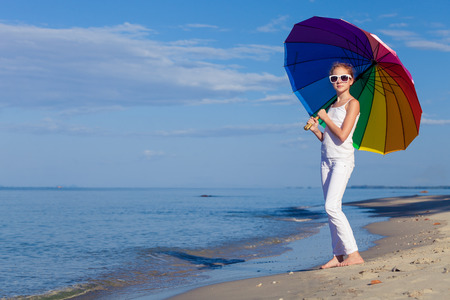 tenager: Ten girl with umbrella standing on the beach at the day time.