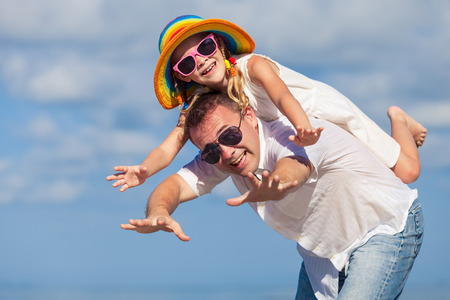 father and child: Father and daughter playing on the beach at the day time. Concept of friendly family. Stock Photo