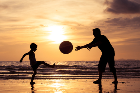 father and son: Father and son playing on the beach at the sunset time. Concept of happy friendly family.