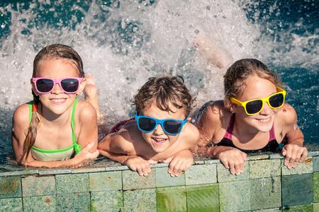 familias jovenes: Tres niños felices jugando en la piscina en el tiempo del día. Concepto de la familia. Foto de archivo