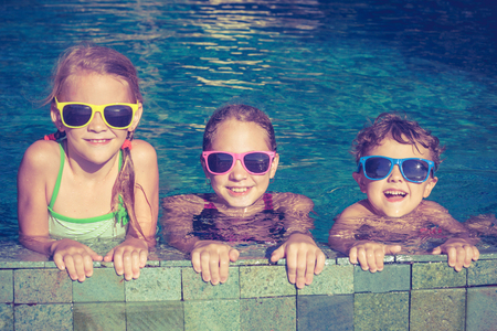 fun in the sun: Three happy children  playing on the swimming pool at the day time. Concept of friendly family.