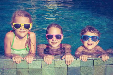 niños nadando: Tres niños felices jugando en la piscina en el tiempo del día. Concepto de la familia. Foto de archivo