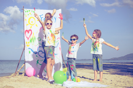 summer holidays: Happy mother and children playing with paint on the beach at the day time. Concept of friendly family. Stock Photo