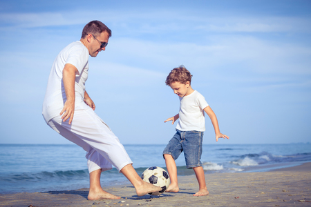 dad son: Father and son playing on the beach at the day time. Concept of friendly family.