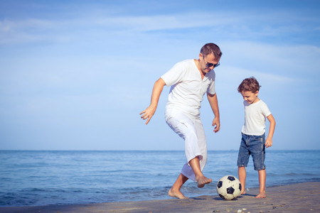 Father and son playing football on the beach at the day time. Concept of friendly family.