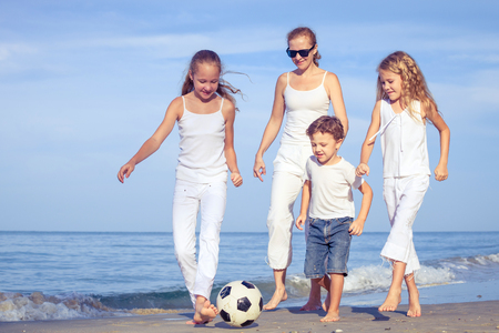 Mother and children playing on the beach at the day time. Concept of friendly family. Stock Photo