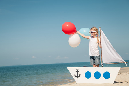 sailor: little girl with balloons standing on the beach at the day time. Concept of happy youth.