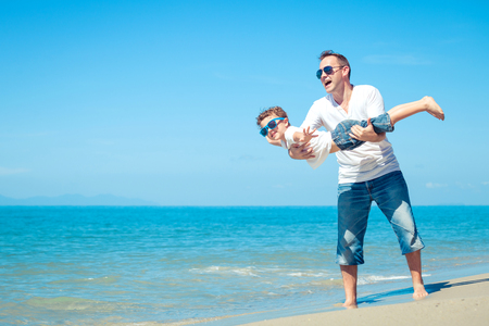 playing in the sea: Father and son playing on the beach at the day time. Concept of happy friendly family.