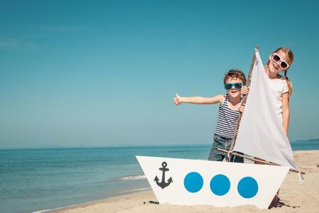 행복한 아이들이 하루에 해변에서 놀고. 행복한 친절한 가족 개념입니다. 스톡 콘텐츠