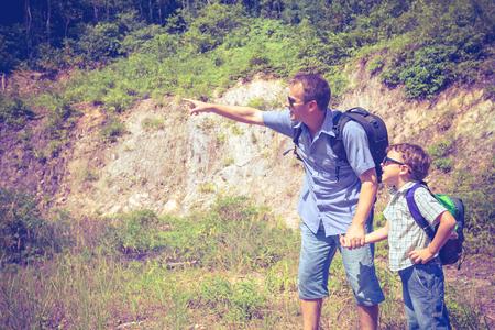 站立在池塘附近的父亲和儿子在天时间。友好的家庭的概念。
