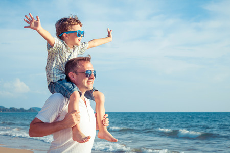 família: Pai e filho brincando na praia no tempo do dia. Conceito de família amigável.