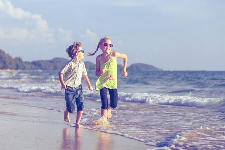 使用在海滩的愉快的孩子在天时间。愉快的友好的姐妹和兄弟的概念。