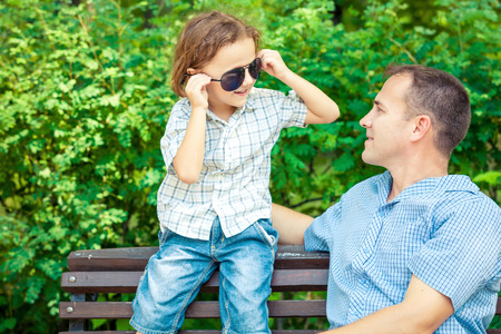 little boys: Father and son playing at the park on bench at the day time. Concept of friendly family.