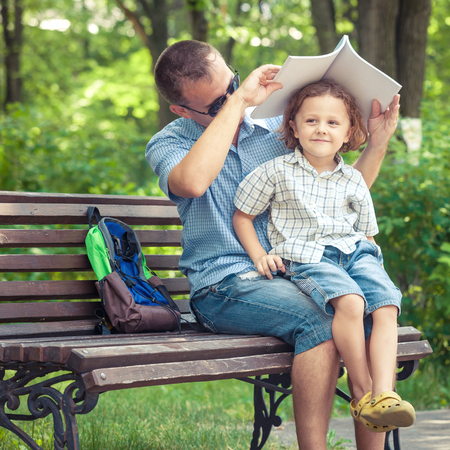 kids outside: Father and son playing at the park on bench at the day time. Concept of friendly family.
