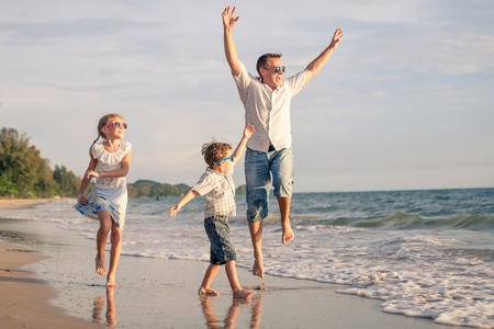 Padre y niños que juegan en la playa en el tiempo del día. Concepto de la familia.