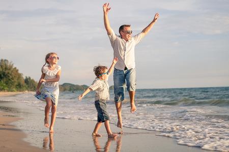 Père et enfants jouant sur la plage au moment de la journée. Concept de la famille.