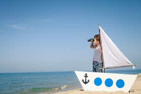 sail boat: little boy standing on the beach at the day time. Stock Photo