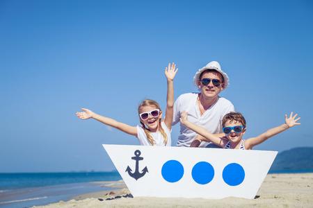 아버지와 낮 시간에 해변에서 노는 아이들. 친화적 인 가족의 개념입니다. 스톡 콘텐츠