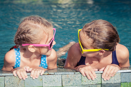 aqua park: Two happy children  playing on the swimming pool in aqua park at the day time. Concept of friendly family. Stock Photo
