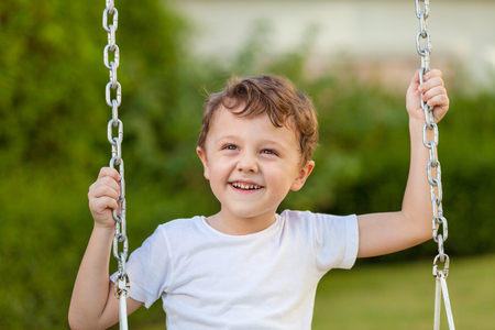 happy little boy playing on playing on the playground at the day time