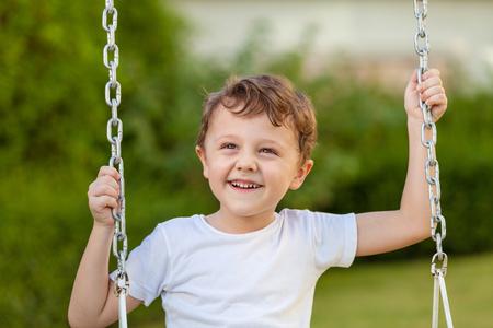 glücklicher kleiner Junge auf dem Spielen auf dem Spielplatz am Tag Zeit zu spielen Lizenzfreie Bilder