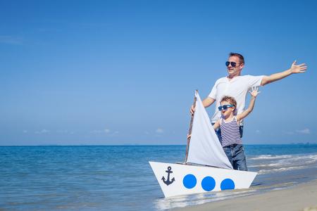 Ojciec i syn gra na plaży w czasie dnia. Koncepcja przyjazny rodzinie.