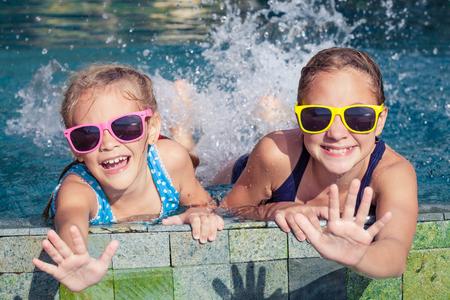 2 幸せな子供が一日の時間でウォーターパークのプールで遊んで。フレンドリーな家族の概念。