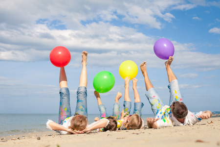 young mother: Happy family with balloons  playing on the beach at the day time. Concept of friendly family. Stock Photo