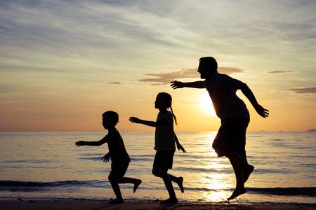 personas saludables: Padre y niños que juegan en la playa en el día de la puesta del sol. Concepto de la familia.