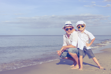 father and son: Father and son playing on the beach at the day time. Concept of friendly family.