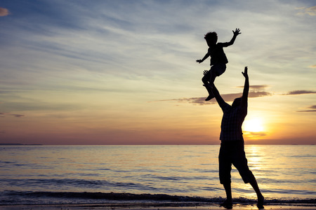 dream: Father and son playing on the beach at the sunset time. Concept of friendly family.