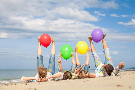 Happy family with balloons  playing on the beach at the day time. Concept of friendly family. Stock Photo
