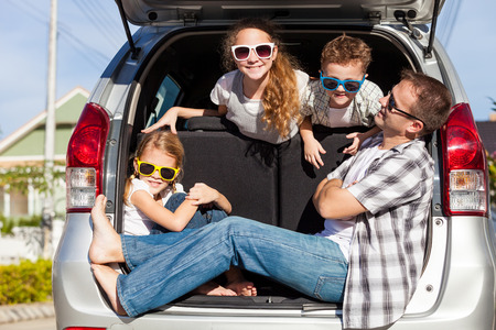 family vacation: Happy family getting ready for road trip on a sunny day.  Concept of friendly family. Stock Photo
