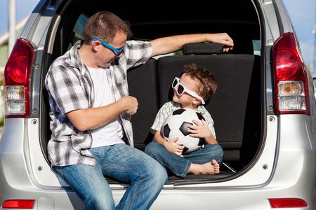 在一个阳光明媚的日子里,快乐的父子俩正在为公路旅行做准备。友好家庭的概念。
