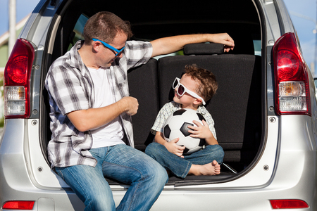 Padre e hijo feliz que consigue listo para viaje por carretera en un día soleado. Concepto de la familia.