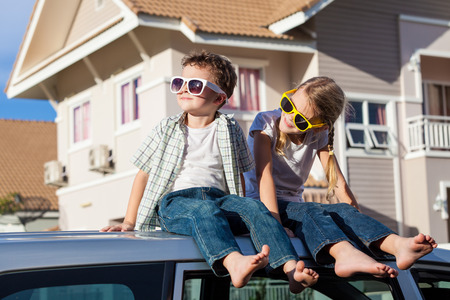 drives: Happy children getting ready for road trip on a sunny day.  Concept of friendly family.