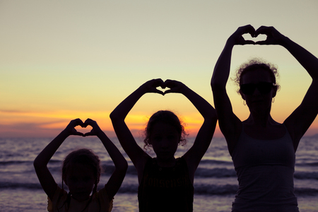 kids outside: Mother and daughters playing on the beach at the sunset time. Concept of happy friendly family. Stock Photo