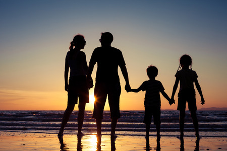 Silhouette of happy family who standing on the beach at the sunset time. Concept of friendly family.