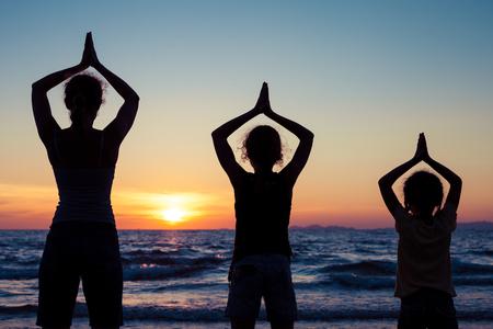 mama e hija: Madre e hijas que juegan en la playa en el momento de la puesta del sol. Concepto de familiar feliz. Foto de archivo